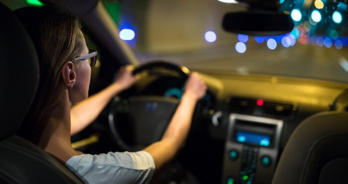 Woman wearing glasses driving at night