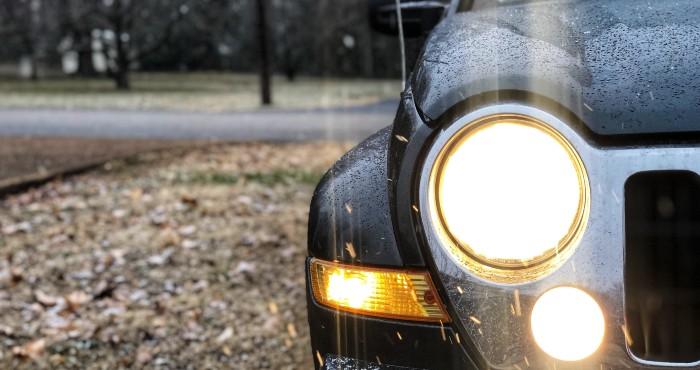 Black car with headlight on