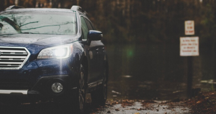 Blue SUV with headlights on