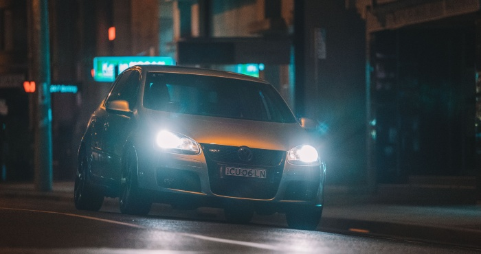 White car at road with headlights on